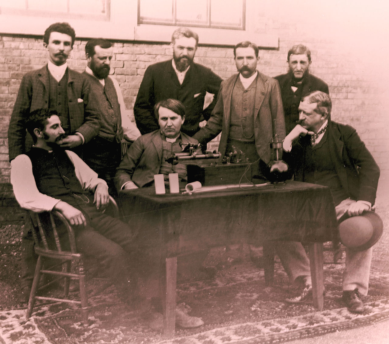 Thomas Edison with his group. The phonograph on the table. Edison is seated in the center, Theo Wangemann is standing behind him.