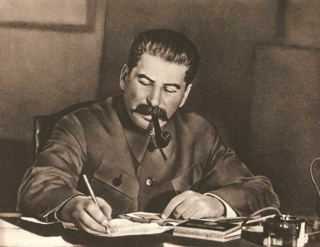 A confident Stalin in his office, seated on his desk and writing a memo.