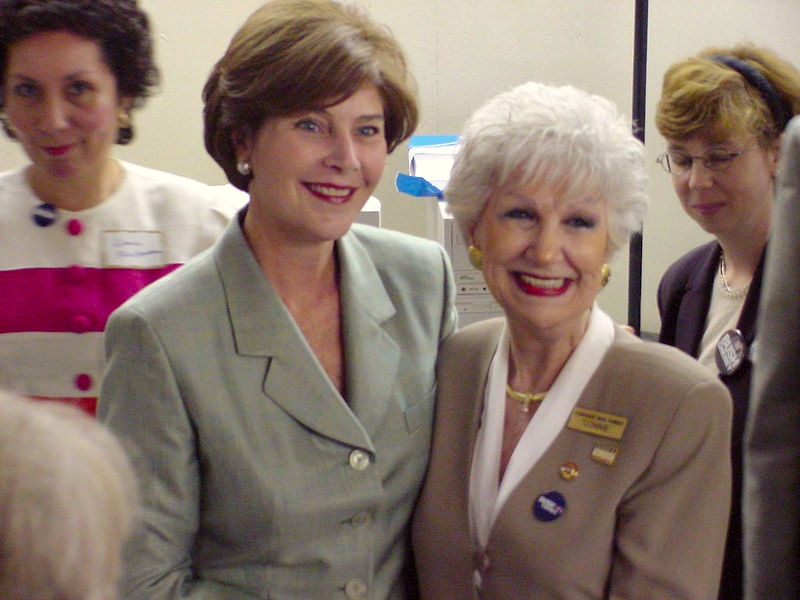 Laura Bush posing for the camera with an aged woman
