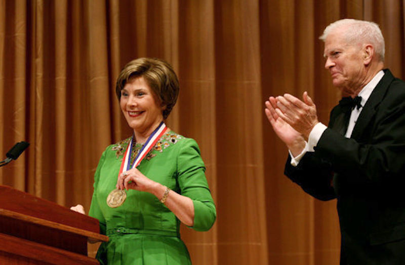 Laura Bush shows her medal on the stage