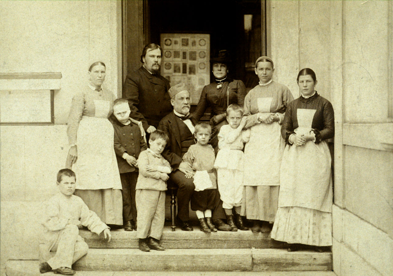Doctor Louis Pasteur seated surround by children and nurses, along with Doctor Leonid Ivanovich Voinov who is standing behind