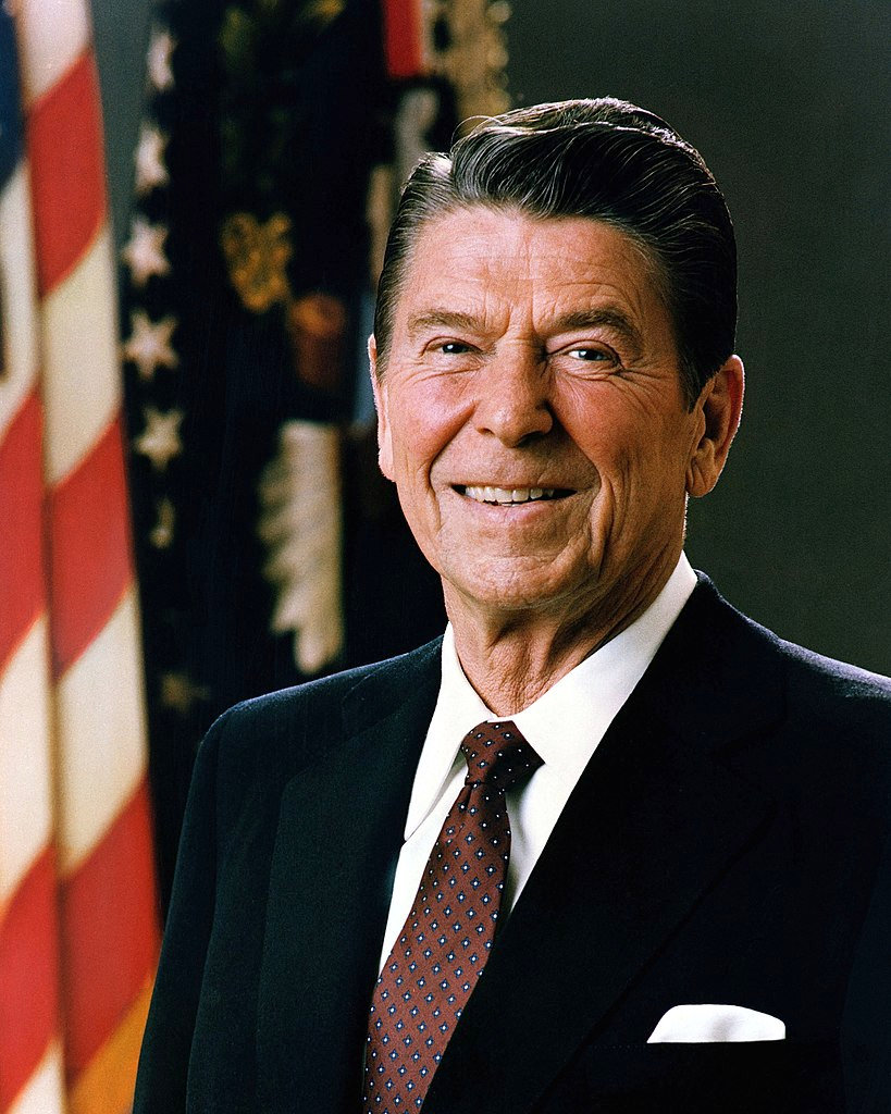 President Ronald Reagan smiling, United States flag in the background