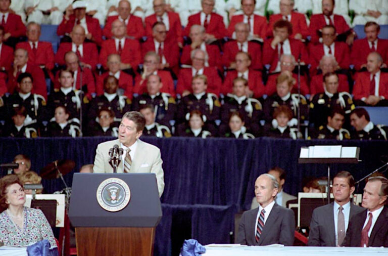 President Reagan addresses the Ecumenical Prayer Breakfast at Reunion Arena in Dallas Texas with George Bush and Ken Cooper looking on.